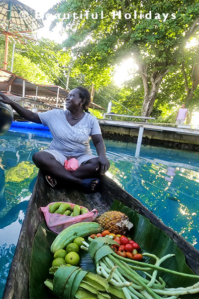 local selling vegetables from dugout canoe in the  solomon islands