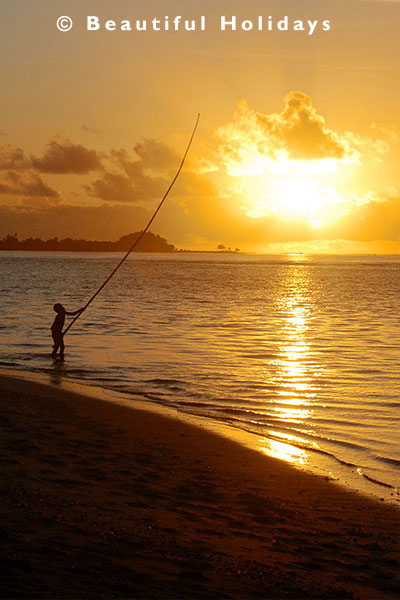 samoan boy fishing from the beachwith bamboo pole